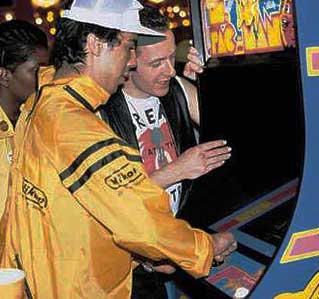 Mick Jones plays Ms. Pac Man while Joe Strummer watches